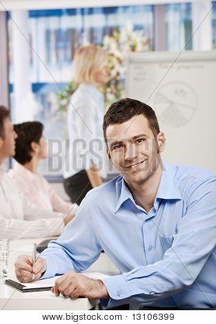 Glücklich kaufmann sitzt am Tisch im Büro Schreiben von Notizen auf Business treffen, Blick in die Kamera, s
