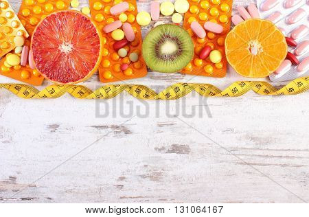 Fruits tape measure and pills tablets or capsules concept of slimming and choice between healthy nutrition and supplements copy space for text