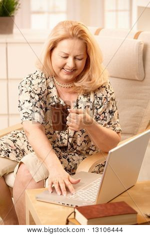 Senior woman drinking coffee, looking at laptop computer with big smile, typing.?