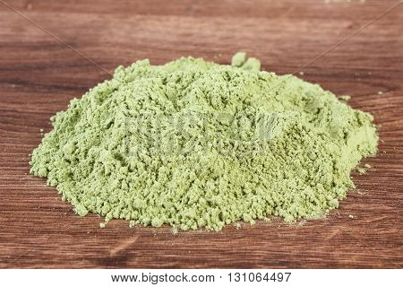 Heap of young powder barley on wooden background healthy nutrition and lifestyle body detox