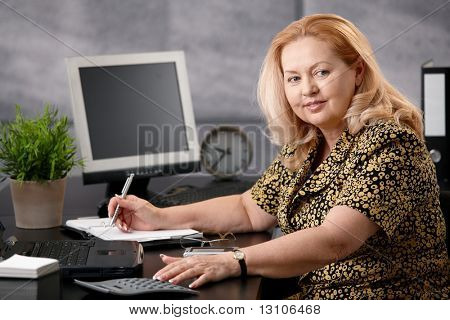 Senior woman sitting at office desk working, writing notes to personal organizer, smiling.?
