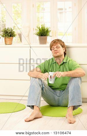 Schöner junger Mann sitzen auf dem Boden des Wohnzimmers, mit Kaffee, lächelnd mit geschlossenen Augen.?