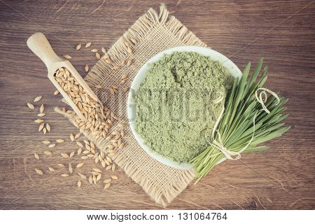 Vintage photo Young powder barley in glass bowl barley grass and grain on jute canvas wooden background healthy nutrition and lifestyle body detox