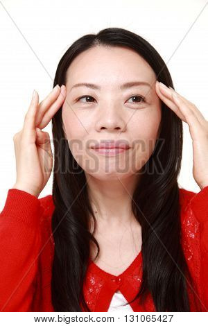 Japanese woman doing self head massage on white background