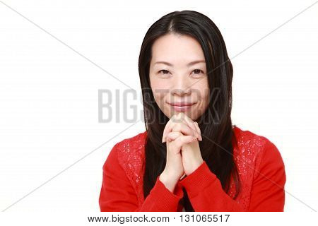 portrait of Japanese woman folding her hands in prayer on white background