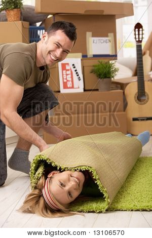 Young couple having fun at moving house, laughing man rolling girlfriend into carpet.
