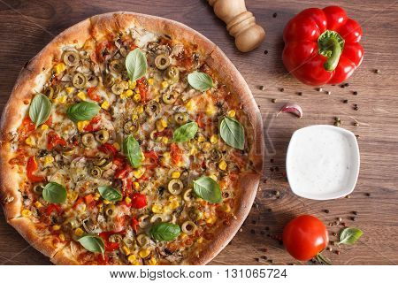 Fresh baked vegetarian pizza with vegetable ingredients and spices on rustic wooden background italian cuisine fast food