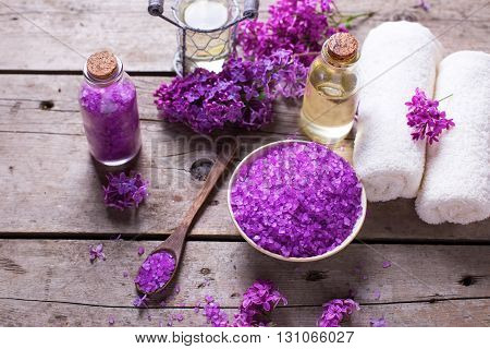 Spa setting. Sea salt candles aroma oil in bottles and towels on vintage wooden background. Selectivee focus.