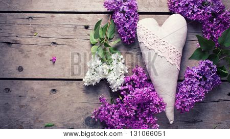 Decorative heart and white and violet lilac flowers on aged wooden planks. Selective focus. Place for text. Toned image.Flat lay.