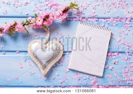 Sakura pink flowers decorative heart and empty notebook on blue wooden planks. Selective focus. Place for text. Flat lay. Top view.