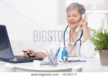 Senior female doctor, working at desk, using laptop computer.