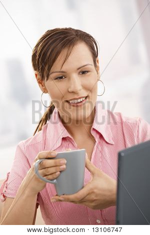 Office worker drinking tea at desk, looking at laptop screen, smiling.