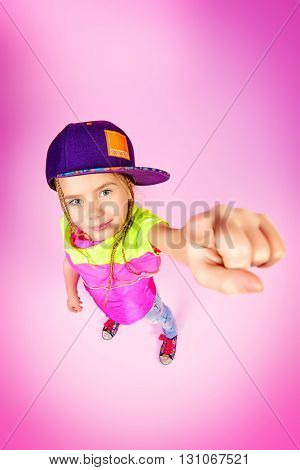 Cute little girl in a cap smiles and shows the index finger at the camera. Kid's style. Happy childhood.