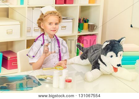 Pretty little girl playing a doctor at home. Different occupations. Children's Health, Pediatrics.