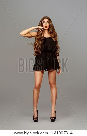 Fashion shot of a gorgeous sexual model with magnificent long hair. Studio shot.