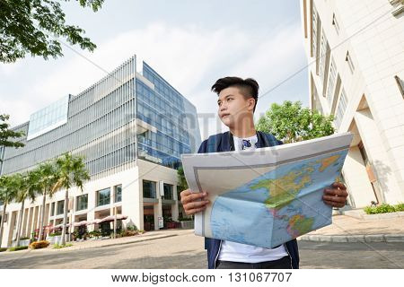 Young Asian man with a map standing in the center of the city
