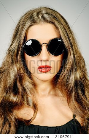 Optics style. Beautiful sexy girl with long wavy hair wearing sunglasses. Fashion studio shot. Cosmetics, make-up. Red lipstick.