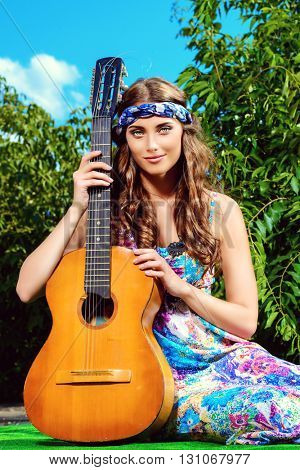 Joyful hippie girl playing the guitar outdoor in the sunny summer day. Child of nature. Lifestyle.
