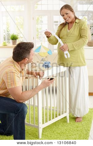 Happy couple expecting baby putting baby bed together in living room, laughing.