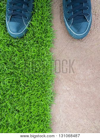 Top View of Two Feet Standing on the Lawn Between the Cement Floor Nature or Building Concept Nature or Man Made Concept Copy Space Vertical