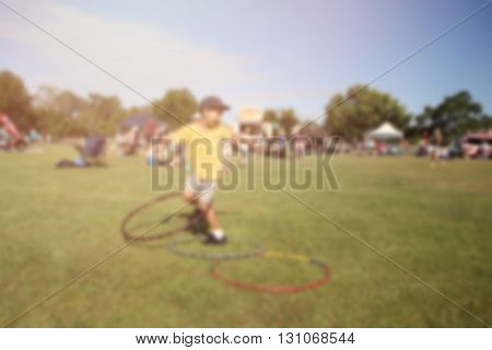 Blur defocused background of boy playing hula hoop in park fair summer festival retro tone