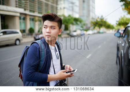 Portrait of Vietnamese young photographer with smartphone standing in street