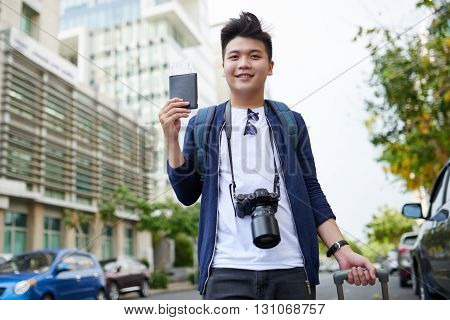Portrait of smiling Asian traveler going to airport