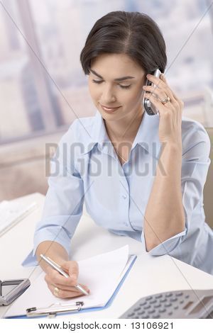 Portrait of smiling businesswoman using cellphone, taking notes at office desk.
