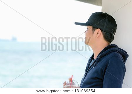 Asian man wearing a blue long sleeve shirt and wearing a hat holding a plastic glass of water by the ocean.