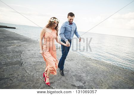 Wedding couple, bride, groom walking and posing on pier.