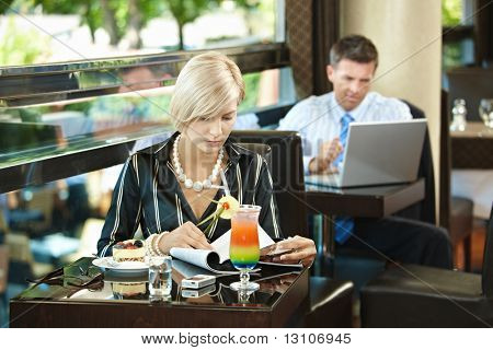 Young woman sitting at table in cafe, reading magazine. Businessman using laptop in the background.