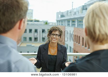 Business people talking on terrace of office building. Businesswoman in front, over the shoulder view.