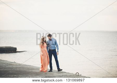Married wedding couple standing on a wharf over the sea.