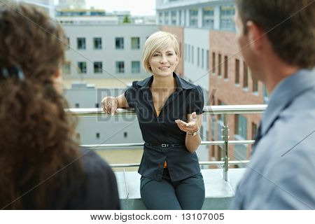Business people talking on terrace of office building. Blond businesswoman in front, over the shoulder view.