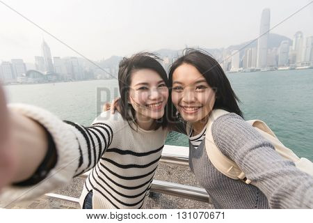 Asian young girls take a selfie with her friends at Victoria Harbor, Hong Kong.