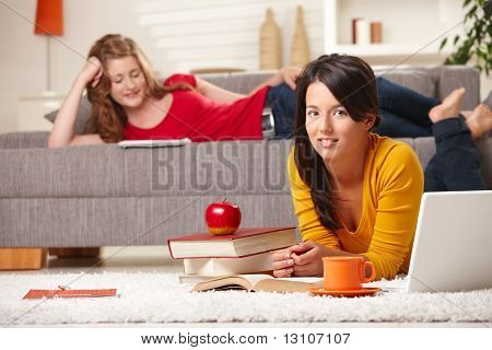 Teenage girls learning at home in living room with books and laptop, girl in front smiling at camera.