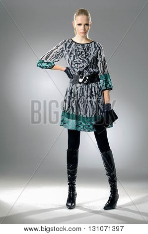 Full body fashion model in fashion dress posing in light background