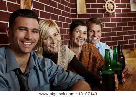 Portrait of happy young people sitting in pub, drinking beer, looking at camera, smiling.