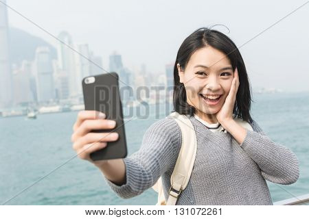 Young Asian woman take a selfie at Victoria Harbor, Hong Kong.