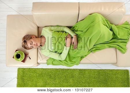 Sleeping woman in high angle view lying on sofa under blanket.