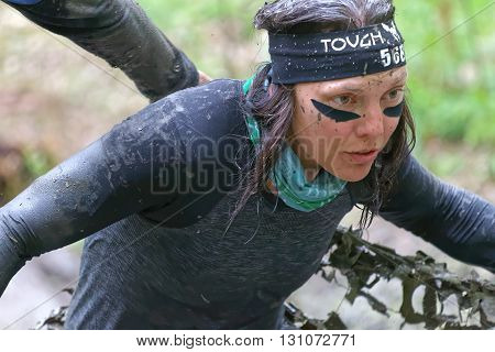 STOCKHOLM SWEDEN - MAY 14 2016: Woman covered with mud fighting to get out of a camouflage net in the obstacle race Tough Viking Event in Sweden April 14 2016