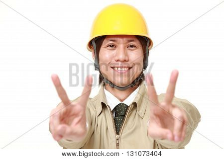 young Japanese construction worker showing a victory sign