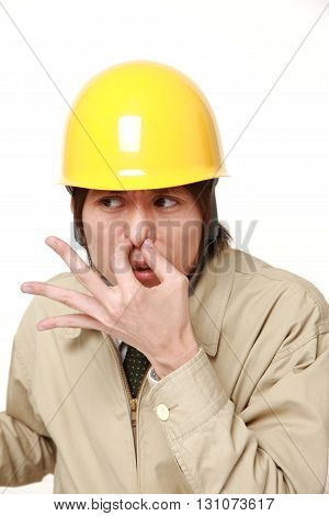 Japanese construction worker holding his nose because of a bad smell