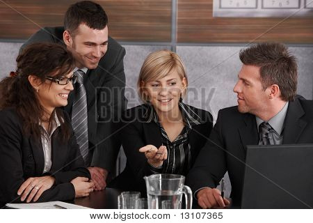 Happy young businesswoman explaining to partners, sitting at meeting table in office, others looking at her, smiling.