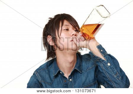 Young Japanese man drinking straight from a bottle