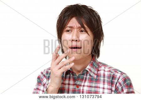 portrait of young Japanese man shocked on white background