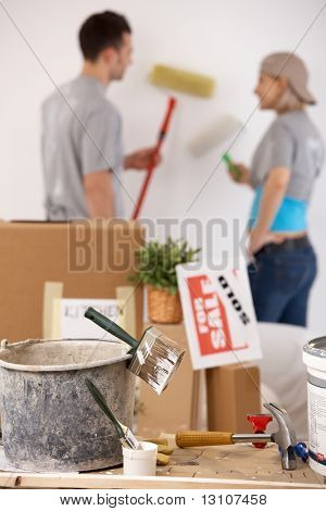 Young couple painting their new house with paint roller, equipment in focus.?