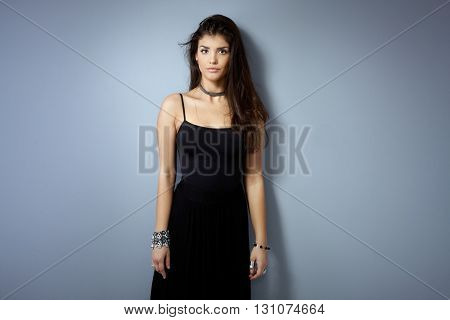 Attractive woman standing against wall in black dress, looking at camera.