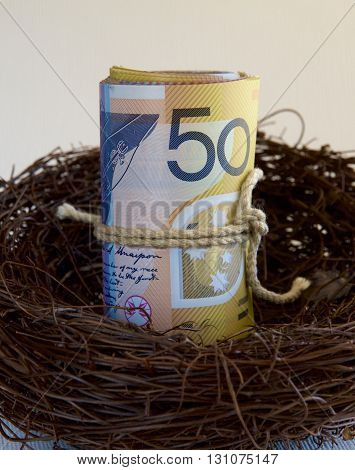 A roll of Australian fifty dollar notes in a nest.