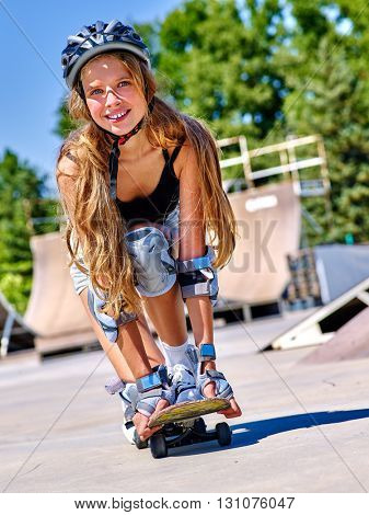 Girl with long hair and helmet skateboarding on his skateboard outdoor.